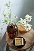 Blume in Apothekerflasche und Seife auf Holzhocker