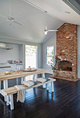 Table with benches and open fireplace in the rustic dining room