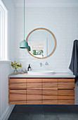 Vanity unit with wooden fronts in the white bathroom