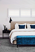 Blue upholstered bench in front of the bed under horizontal louvre windows