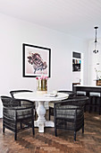 Black wicker chairs on white baluster table on herringbone parquet
