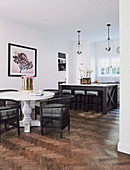 Black wicker chairs on white baluster table in front of open kitchen
