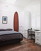 Surfboard next to the bed in the bedroom with a desk