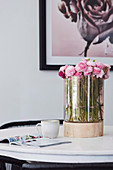 Pink ranunculus in a glass vase with wooden base on the table