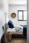 Wooden bed in a simple bedroom with natural materials