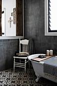 Old chair next to free-standing bathtub on sample floor in bathroom