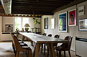 Long wooden dining table below mezzanine in renovated Antwerp house