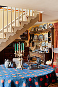 Antique sewing machine and candelabra on round table in front of old dresser crammed with crockery
