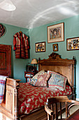 Antique wooden bed in bedroom with turquoise walls in English country house