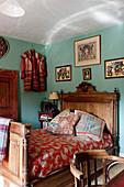 Antikes Holzbett in Schlafraum mit türkisfarbenen Wänden in englischem Landhaus