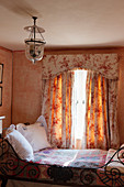 Ornate metal bed below window with toile-de-Jouy curtains and pelmet