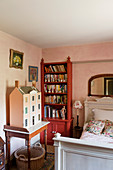 Old dolls' house on console table, red bookcase and white wooden bed in bedroom