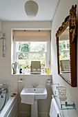 Narrow Edwardian-style bathroom with sink below window