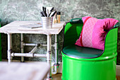 Green-painted barrel chair and vintage-style table made from steel pipes
