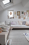Scatter cushions on pale couch below gallery of artworks in bright, attic living room
