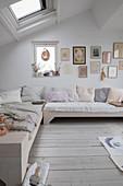 Helles Bettsofa mit Kissen, darüber Kunstsammlung in hellem Wohnzimmer im Dachgeschoss