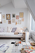 Scatter cushions on pale sofa below gallery of artworks in bright living room