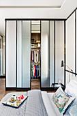 Blick über Doppelbett in begehbaren Kleiderschrank mit Schiebetüren