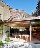 Blick in modernen Anbau mit Verglasung und trichterförmigem Dach