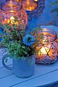 Meadowsweet and love-in-a-mist in mug next to candle lantern