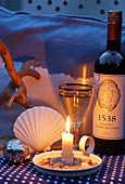 Twilight scene with white wine, candlelight and maritime ornaments