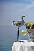 Bird ornament and glass of white wine on table with sea in background
