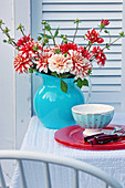 Bouquet of dahlias in blue jug and place setting on garden table