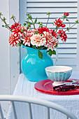 Dahlienstrauß in blauer Krugvase und Gedeck auf Gartentisch