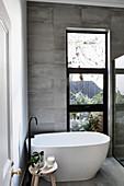 Modern freestanding bathtub by the window in a gray tiled bathroom