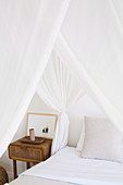 Rustic bedside table next to the bed with white canopy