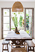 Bast lamp above the rustic dining table in front of the garden access