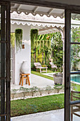 View through the rung door into the exotic garden with pool