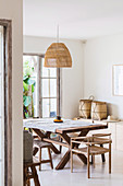 Bast lamp above the rustic wooden table in the exotic dining room
