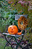 Halloween pumpkin and wreath of sycamore leaves on garden chair