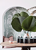 Decorative glass bottles and green palm fan leaves in vase on table in front of alcove