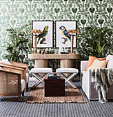 Safari-style seating area in front of green wallpaper with palm tree motifs
