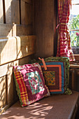 Colourful scatter cushions on bench in sunny farmhouse parlour