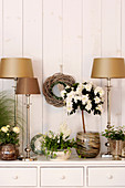 Potted azalea surrounded by gold table lamps