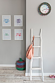 Rustic wooden ladder used as coat stand in grey hallway