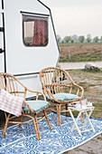 Zwei Bambusstühle mit Klapptisch vor renoviertem 80er-Jahre Wohnwagen