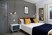 Double bed, night stand and pendant lamps in bedroom with dark grey wall