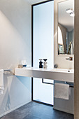 Waschtisch vor raumhohem Fenster in elegantem Bad