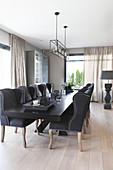 Elegant upholstered chairs around black table in dining area