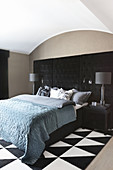 Double bed against black, button-tufted panel in bedroom with black-and-white rug