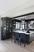 Display cabinet, island counter and black walls in elegant open-plan kitchen