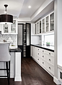 White counter with black worksurface in open-plan kitchen