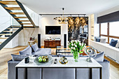 Console table against back of sofa in elegant lounge with window seats