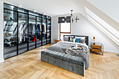 Double bed and fitted wardrobes with glass doors in bedroom