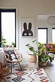 Rattanstuhl und Monstera auf buntem Ethno-Teppich vorm Hasen-Bild