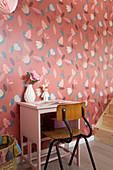 Alter Stuhl und rosafarbenes Tischchen vor rot geblümter Tapete
